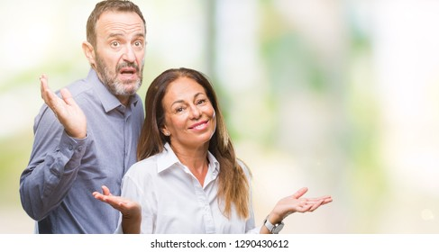 Middle age hispanic business couple over isolated background clueless and confused expression with arms and hands raised. Doubt concept.