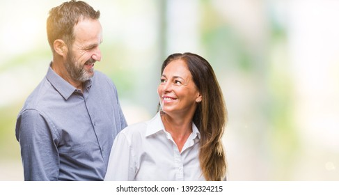 Middle age hispanic business couple over isolated background with serious expression on face. Simple and natural looking at the camera.