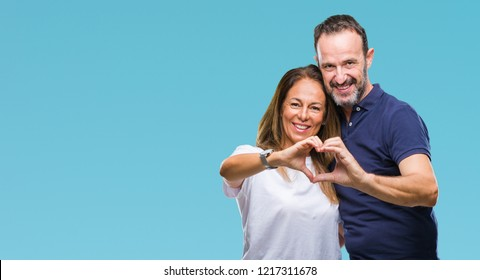 Middle age hispanic casual couple over isolated background smiling in love showing heart symbol and shape with hands. Romantic concept.