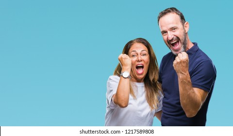 Middle age hispanic casual couple over isolated background very happy and excited doing winner gesture with arms raised, smiling and screaming for success. Celebration concept.