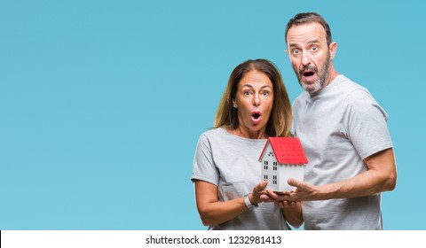 Middle age hispanic casual couple buying new house over isolated background scared in shock with a surprise face, afraid and excited with fear expression