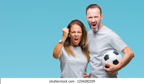 Middle age hispanic couple holding football soccer ball over isolated background annoyed and frustrated shouting with anger, crazy and yelling with raised hand, anger concept