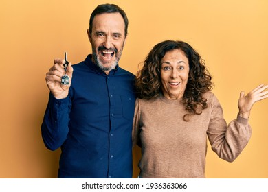 Middle age hispanic couple holding keys of new home celebrating victory with happy smile and winner expression with raised hands