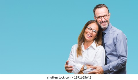 Middle age hispanic couple in love wearing glasses over isolated background happy face smiling with crossed arms looking at the camera. Positive person.