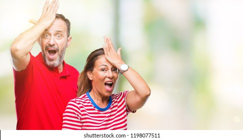 Middle age hispanic couple in love over isolated background surprised with hand on head for mistake, remember error. Forgot, bad memory concept.
