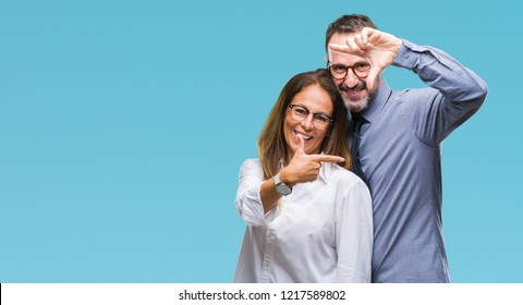 Middle age hispanic couple in love wearing glasses over isolated background smiling making frame with hands and fingers with happy face. Creativity and photography concept.