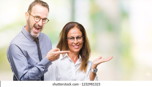 Middle age hispanic couple in love wearing glasses over isolated background amazed and smiling to the camera while presenting with hand and pointing with finger.