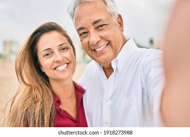 Middle age hispanic couple smiling happy making selfie by the camera at the beach.