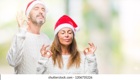 Middle age hispanic couple wearing christmas hat over isolated background relax and smiling with eyes closed doing meditation gesture with fingers. Yoga concept.