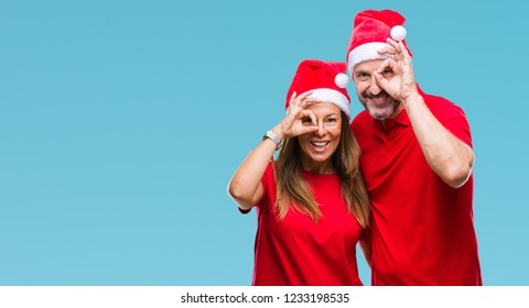 Middle age hispanic couple wearing christmas hat over isolated background doing ok gesture with hand smiling, eye looking through fingers with happy face.