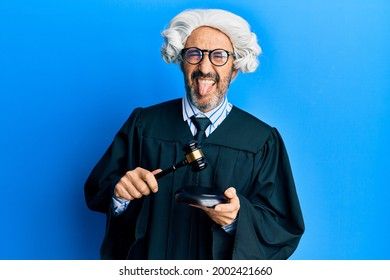 Middle age hispanic man using gavel sticking tongue out happy with funny expression.