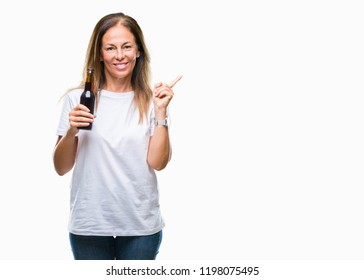 Middle age hispanic woman drinking beer over isolated background very happy pointing with hand and finger to the side