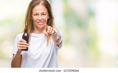 Middle age hispanic woman drinking beer over isolated background pointing with finger to the camera and to you, hand sign, positive and confident gesture from the front