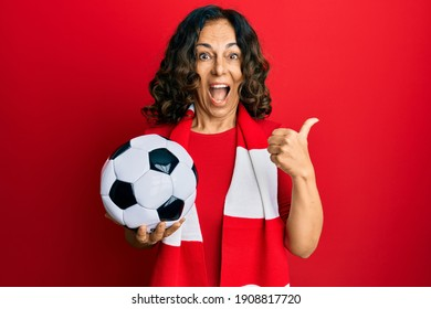 Middle age hispanic woman football hooligan holding ball pointing thumb up to the side smiling happy with open mouth