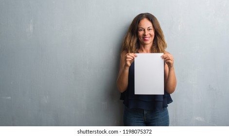Middle age hispanic woman holding bank paper sheet with a happy face standing and smiling with a confident smile showing teeth