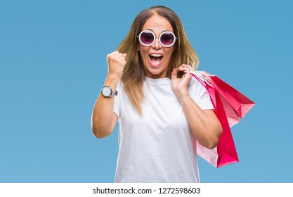 Middle age hispanic woman holding shopping bags on sales over isolated background screaming proud and celebrating victory and success very excited, cheering emotion