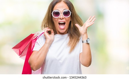 Middle age hispanic woman holding shopping bags on sales over isolated background very happy and excited, winner expression celebrating victory screaming with big smile and raised hands
