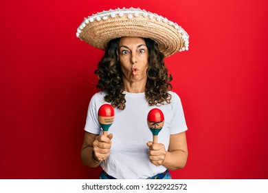 Middle age hispanic woman holding mexican hat playing maracas making fish face with mouth and squinting eyes, crazy and comical.