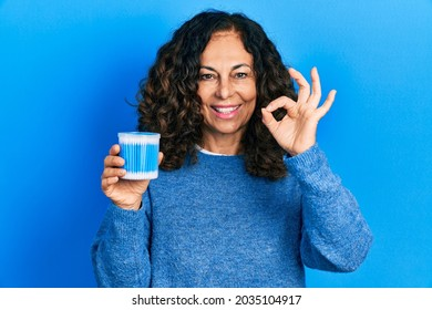 Middle age hispanic woman holding earwax cotton remover doing ok sign with fingers, smiling friendly gesturing excellent symbol