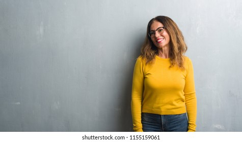 Middle age hispanic woman over grey wall wearing glasses looking away to side with smile on face, natural expression. Laughing confident.