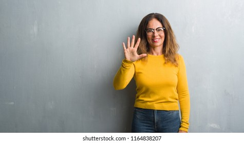 Middle age hispanic woman over grey wall wearing glasses showing and pointing up with fingers number five while smiling confident and happy.