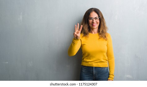 Middle age hispanic woman over grey wall wearing glasses showing and pointing up with fingers number three while smiling confident and happy.