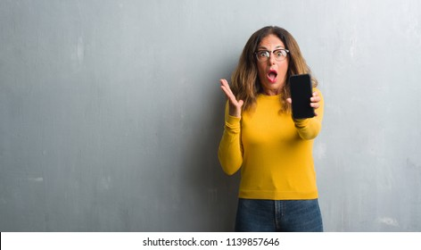 Middle age hispanic woman showing smarphone screen very happy and excited, winner expression celebrating victory screaming with big smile and raised hands
