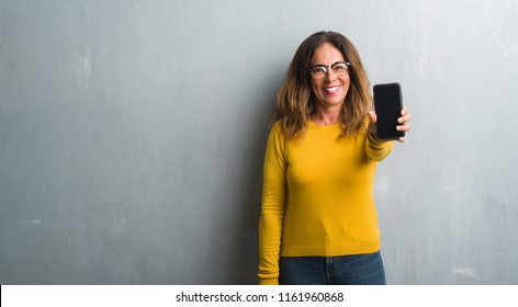 Middle age hispanic woman showing smarphone screen with a happy face standing and smiling with a confident smile showing teeth