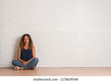 Middle age hispanic woman sitting on the floor over white brick wall skeptic and nervous, frowning upset because of problem. Negative person.