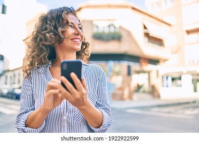 Middle age hispanic woman smiling happy and using smartphone at the city.