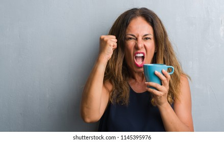 Middle age hispanic woman standing over grey grunge wall drinking cup of coffee annoyed and frustrated shouting with anger, crazy and yelling with raised hand, anger concept