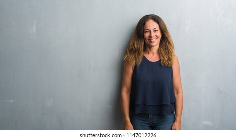 Middle age hispanic woman standing over grey grunge wall with a happy and cool smile on face. Lucky person.