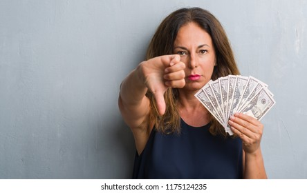 Middle age hispanic woman standing over grey grunge wall holding dollars with angry face, negative sign showing dislike with thumbs down, rejection concept