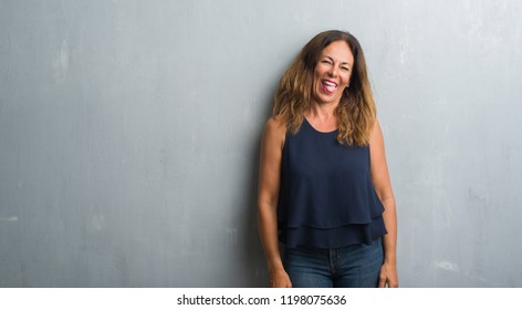 Middle age hispanic woman standing over grey grunge wall sticking tongue out happy with funny expression. Emotion concept.