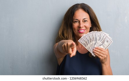 Middle age hispanic woman standing over grey grunge wall holding dollars pointing with finger to the camera and to you, hand sign, positive and confident gesture from the front