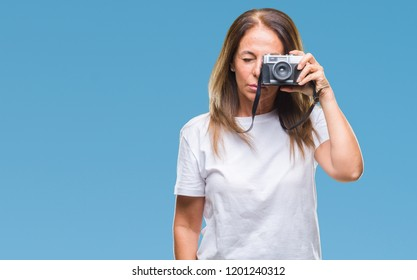 Middle age hispanic woman taking pictures using vintage photo camera over isolated background with a confident expression on smart face thinking serious