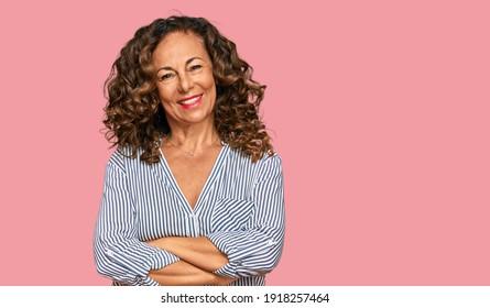 Eine hispanische Frau im Mittelalter, die ungezwungene Kleidung trägt, hat ein fröhliches Gesicht, das mit gekreuzten Armen lächelt und die Kamera anschaut. positive Person.