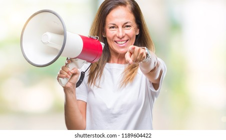 Middle age hispanic woman yelling through megaphone over isolated background pointing with finger to the camera and to you, hand sign