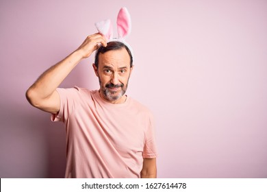Middle age hoary man wearing bunny ears standing over isolated pink background confuse and wonder about question. Uncertain with doubt, thinking with hand on head. Pensive concept.