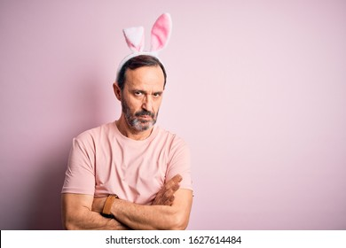 Middle age hoary man wearing bunny ears standing over isolated pink background skeptic and nervous, disapproving expression on face with crossed arms. Negative person.