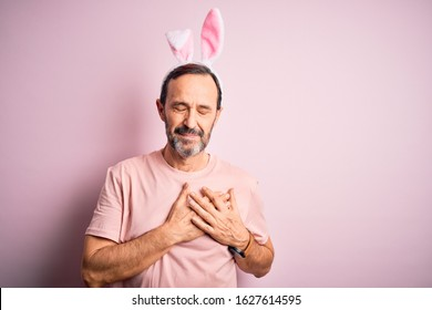 Middle age hoary man wearing bunny ears standing over isolated pink background smiling with hands on chest with closed eyes and grateful gesture on face. Health concept.