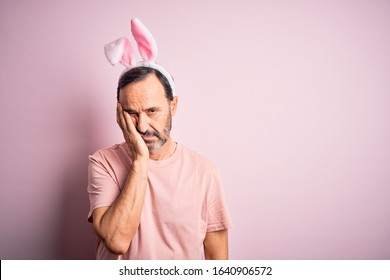 Middle age hoary man wearing bunny ears standing over isolated pink background thinking looking tired and bored with depression problems with crossed arms.