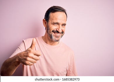 Middle age hoary man wearing casual t-shirt standing over isolated pink background doing happy thumbs up gesture with hand. Approving expression looking at the camera showing success.