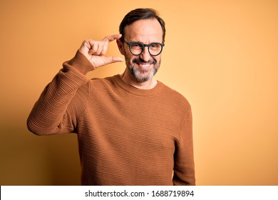 Middle age hoary man wearing brown sweater and glasses over isolated yellow background smiling and confident gesturing with hand doing small size sign with fingers looking and the camera. Measure