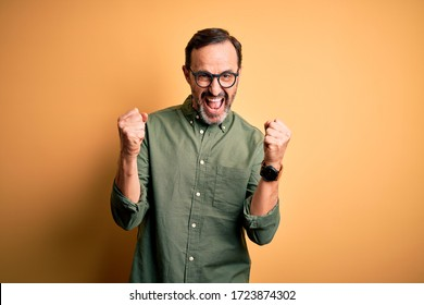Middle age hoary man wearing casual green shirt and glasses over isolated yellow background celebrating surprised and amazed for success with arms raised and open eyes. Winner concept.