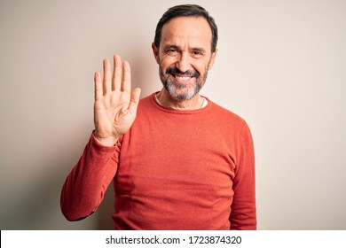 Middle age hoary man wearing casual orange sweater standing over isolated white background Waiving saying hello happy and smiling, friendly welcome gesture