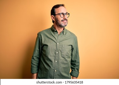 Middle age hoary man wearing casual green shirt and glasses over isolated yellow background looking away to side with smile on face, natural expression. Laughing confident.