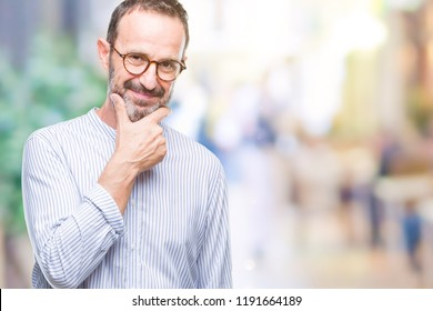 Middle age hoary senior man wearing glasses over isolated background looking confident at the camera with smile with crossed arms and hand raised on chin. Thinking positive.