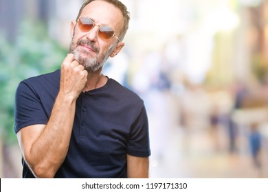 Middle age hoary senior man wearing sunglasses over isolated background with hand on chin thinking about question, pensive expression. Smiling with thoughtful face. Doubt concept.
