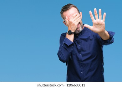 Middle age hoary senior man over isolated background covering eyes with hands and doing stop gesture with sad and fear expression. Embarrassed and negative concept.